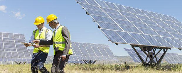Trabajadores caminando junto a paneles solares en un paisaje rural
